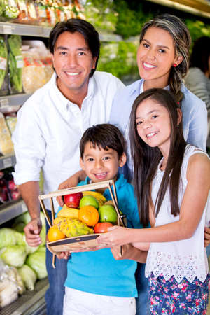 Healthy family at the local market buying fruits photo