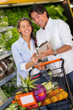 Couple with shopping list on a tablet computer at the supermarket photo