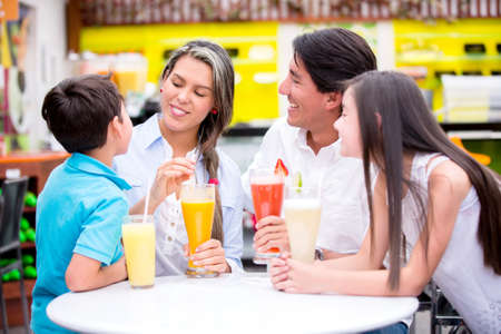 diner: Happy family at a cafeteria drinking juices