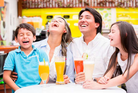 Happy family at the diner enjoying together and laughing photo