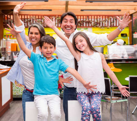 Excited family with arms up at a restaurant photo