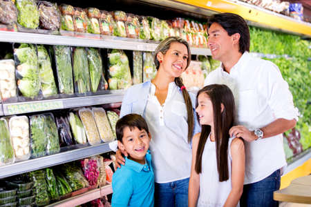 Happy family at the supermarket shopping for groceries photo