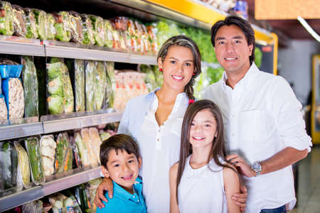 people buying: Happy family at the supermarket shopping for groceries