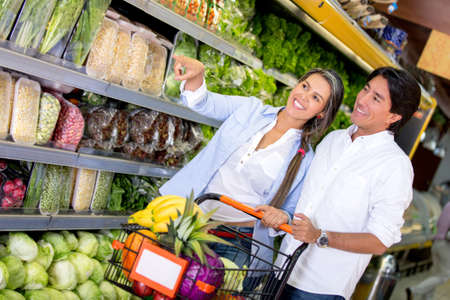 Happy couple at the supermarket buying groceries photo