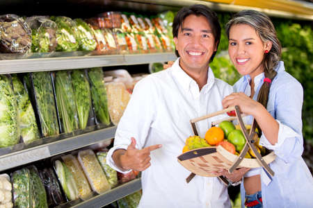 healthy economy: Healthy eating couple buying fruits at the market Stock Photo