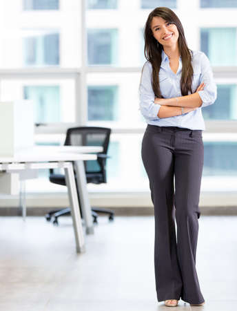 business woman: Happy business woman at the office smiling Stock Photo