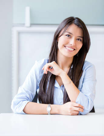 Confident businesswoman sitting at the office and smiling photo