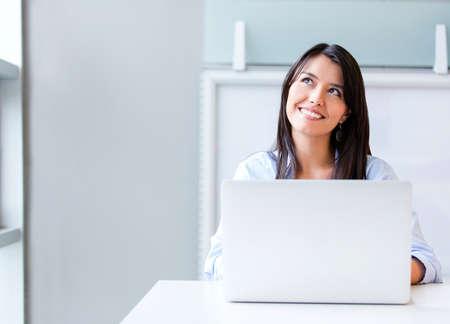 mujer pensar: Mujer de negocios pensativo que trabaja en un ordenador port�til