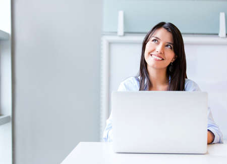 daydreaming: Thoughtful business woman working on a laptop Stock Photo