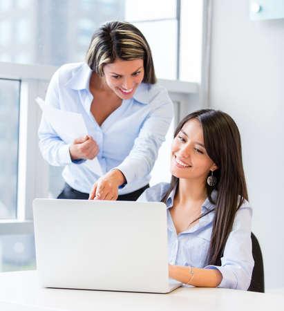 mujeres trabajando: Las mujeres de negocios que trabajan en la oficina en un ordenador portátil Foto de archivo