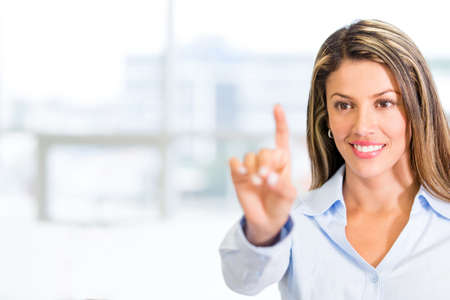 Businesswoman touching an imaginary screen with her finger photo