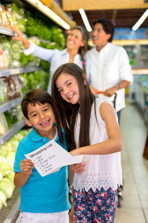 Kids at the supermarket holding a shopping list photo