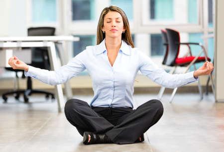 pausa: Mujer de negocios que hace yoga en la oficina