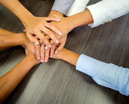 business meetings: Business team in a meeting with their hands together Stock Photo