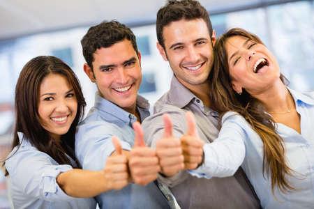 trabajadores: Grupo empresarial con �xito con los pulgares para arriba en la oficina Foto de archivo