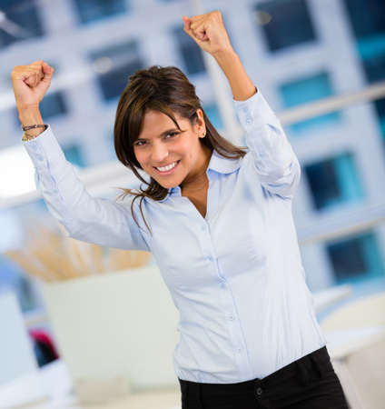 Businesswoman celebrating her triumph with arms up photo