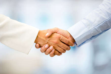 welcome people: Successful business people handshaking closing a deal