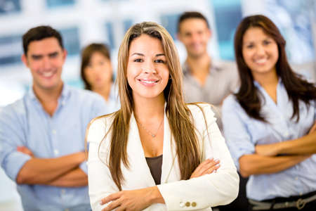 Businesswoman leading a business group and looking happy photo