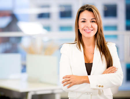 business woman: Confident business woman at the office with arms crossed Stock Photo
