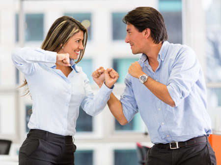 Competitive business couple fighting at the office photo