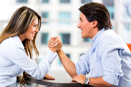 Business couple  arm wrestling at the office photo