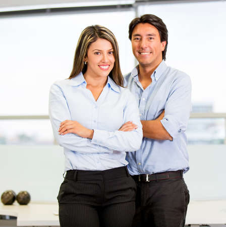 Happy business couple with arms crossed at the office photo