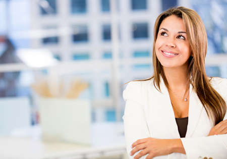 Pensive business woman at the office looking happy Stock Photo - 18021208