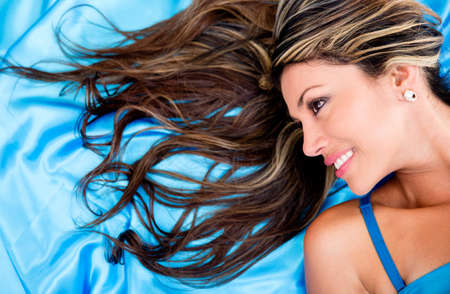 Woman with beautiful hair lying on a blue fabric photo