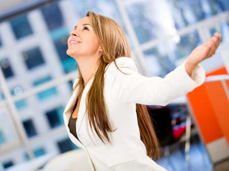 Successful business woman with arms open at the office Stock Photo - 18038094