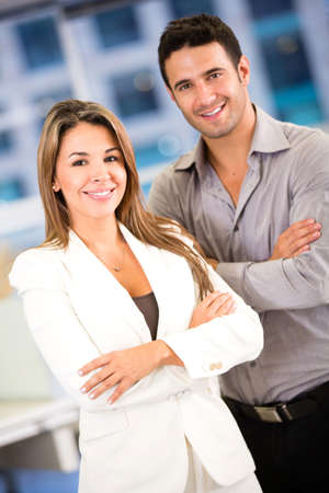 business couple: Successful business couple at the office looking confident