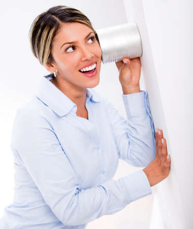 Businesswoman listening to secrets behind a wall Stock Photo - 18038132