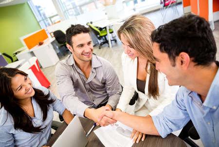 n�gocier: Les gens d'affaires de cl�ture un accord et poign�es de main au bureau