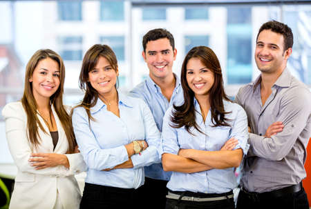 entrepreneur: Happy business team with arms crossed at the office Stock Photo