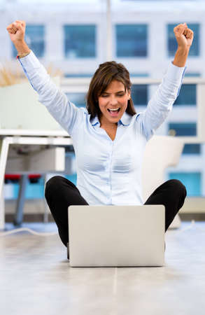 Business woman enjoying her online success at the office Stock Photo - 18055410