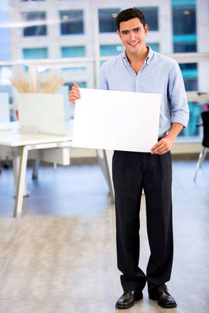 Businessman holding a banner at the office Stock Photo - 18055422