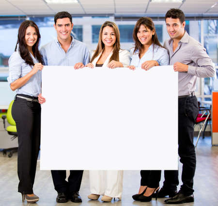 Business group holding a banner at the office photo