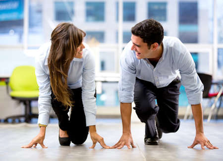 coworker: Competitive business couple ready for a race at the office Stock Photo