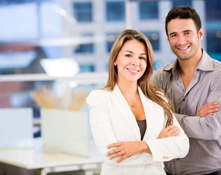 business couple: Happy business couple with arms crossed at the office