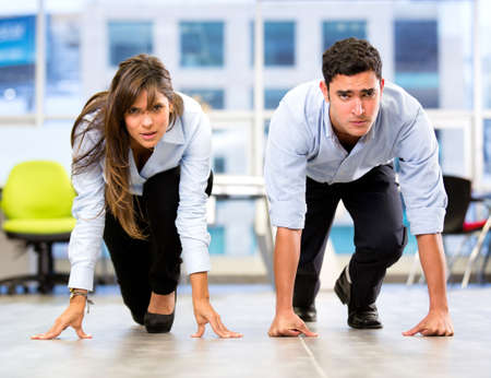 business competition: Competitive business couple racing at the office