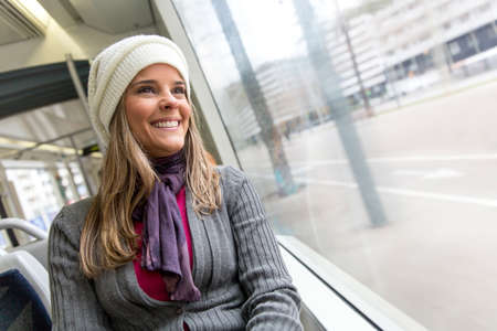 Woman riding in a bus and looking happy Stock Photo - 18489651