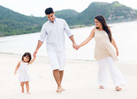 Beautiful family walking at the beach enjoying their holidays photo