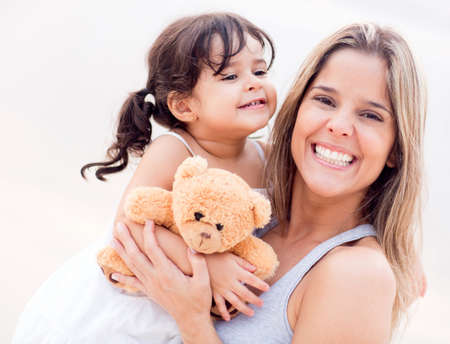 mothers: Mother and daughter portrait with a teddy bear