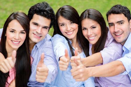 grupo de personas: Feliz grupo de amigos con los pulgares para arriba al aire libre Foto de archivo