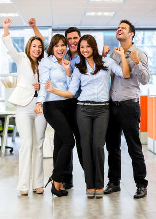 Entrepreneurs: Successful business team at the office with arms up