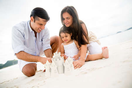 Happy family at the beach making sand castles photo