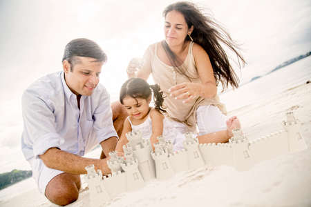Beautiful family on holidays building sand castles at the beach photo
