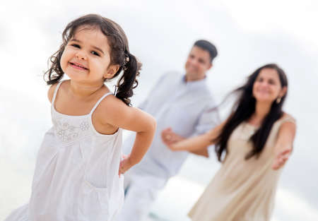 Happy girl enjoying with her family at the beach Stock Photo - 18561569
