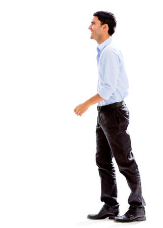 standing man: Business man walking to the side - isolated over a white background Stock Photo
