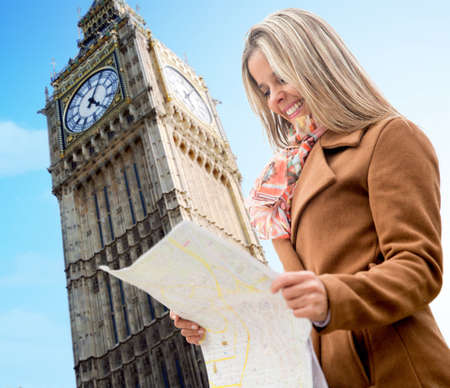 Happy woman sightseeing in London holding a map and smiling Stock Photo - 18568731