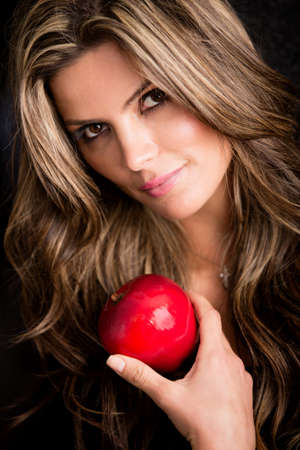 Beautiful woman portrait holding an apple - isolated over black photo